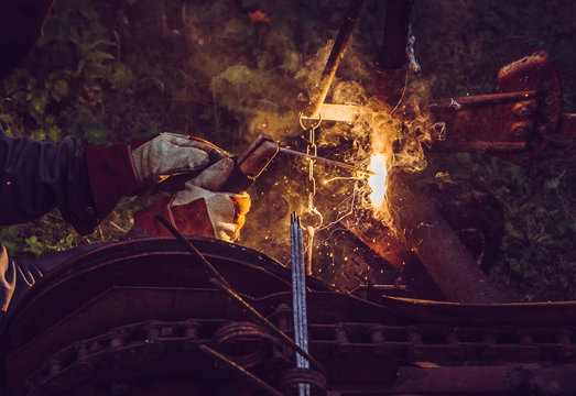 Man using welding machine stick to cut melt iron metal construction outdoors, wearing protective mask and gloves, sparks fly.