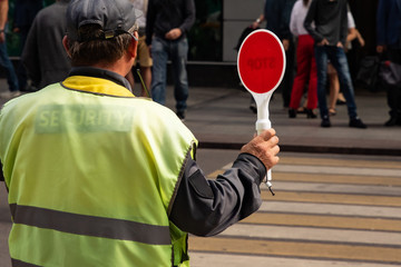 traffic controller with a stop sign helps pedestrians cross the road