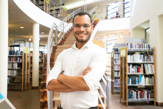 Smiling African American man posing at public library. Front view of confident young guy with crossed arms standing in front of stairs. Knowledge concept