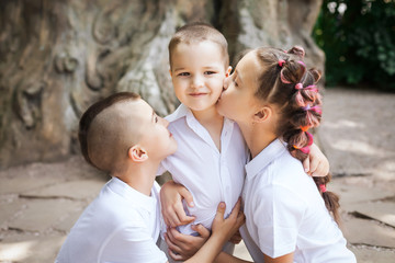 three happy joyful cute children wearing white shirts. lovely girl is kissing her small brother in the park. concept of love and family