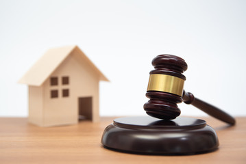 Auction or law concept. Miniature House on wooden table and judge gavel.