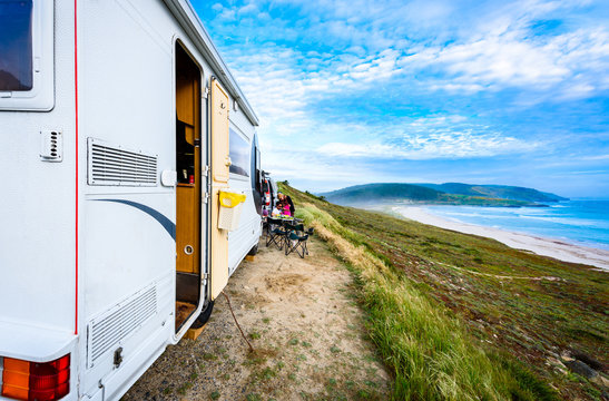 Motorhome RV and campervan are parked on a beach.