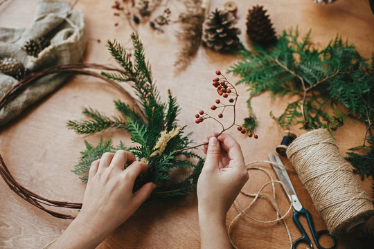 Making rustic christmas wreath. Hands holding berries, fir branches, pine cones, thread, scissors on wooden table.  Authentic rural wreath. Christmas wreath workshop