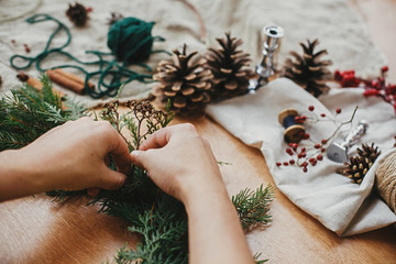 Making rustic Christmas wreath. Hands holding herbs and  fir branches, pine cones, thread, berries, cinnamon on wooden table. Christmas wreath workshop. Authentic stylish still life.