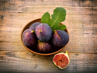 Fresh figs with leaves on an old wooden background. Sweet and healthy fruits.