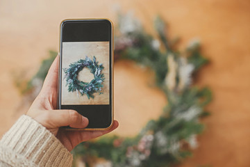 Hand holding phone and taking photo of rustic Christmas wreath flat lay. Christmas mockup. Hipster girl making photo of christmas wreath on smartphone. Merry Christmas