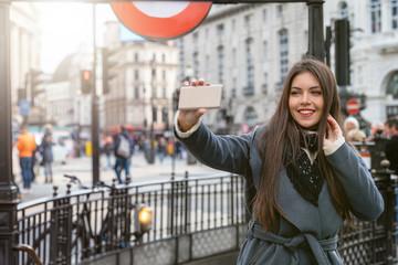 Touristin am Piccadilly Circus in London machr Selfie Fotos von sich auf einen Sightseeing Trip durch die Stadt, Großbritannien