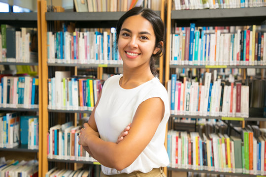 Smiling Asian woman posing at public library. Front view of smiling lady with crossed arms posing in front of bookshelves. Knowledge concept