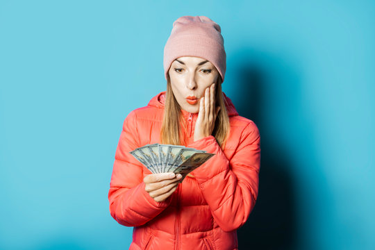 Beautiful young woman in a hat and a winter jacket with a surprised face holds money on a blue background. Concept winter, change of season, success, luck, win, credit, sale