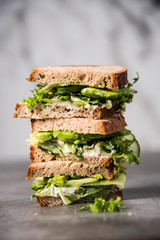 Three sandwiches on top of each other. Layered rustic breads with avocado and fresh salad on grey background.