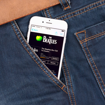 Apple iPhone in jeans pocket displaying Beatles band music in iTunes. The Beatles were an English rock band that formed in Liverpool, in 1960.