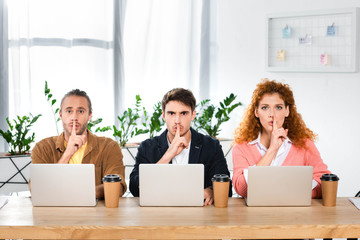 three friends sitting at table and showing shh gestures in office