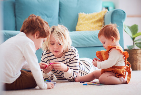 cute kids, siblings playing together on the floor at home