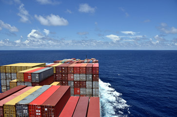 Large cargo container ship loaded with colorful containers sailing through a blue ocean.