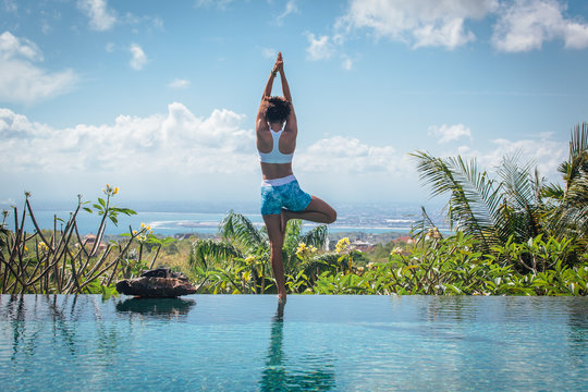 Young woman practicing yoga pose asana on the edge of infinity pool with breathtaking view at the villa in Bali