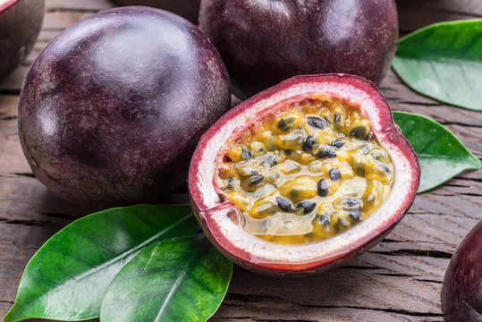 Passion fruits and its cross section with pulpy juice filled with seeds. Wooden background.