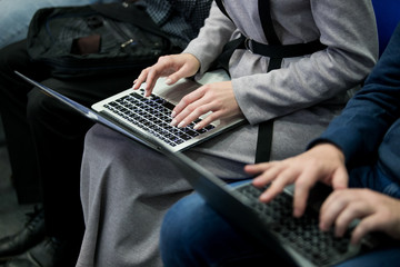 A picture of laptop. Girl holds it on her lap. She has her fingers on its keyboard. Woman types. She works