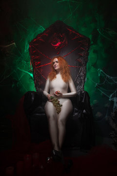 evil whitch in naked costume ready for halloween party and posing in hell studio background with fog