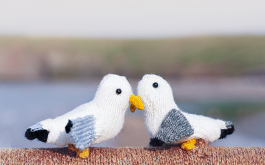 Two knitting cute little birds kissing standing on rope by the sea with blurry cliff background, Image with copy space for letter or message, Concept for love card and Valentine