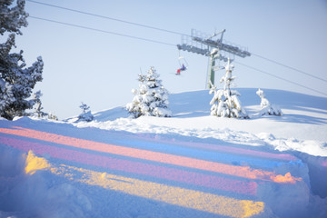 Multicoloured reflections on the snow and skiing lift behind them
