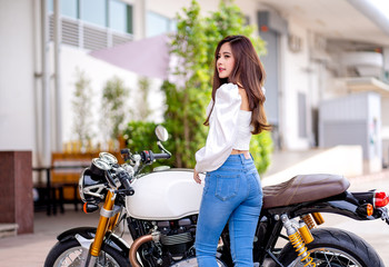 Outdoor lifestyle portrait of asian beautiful biker girl and motorcycle