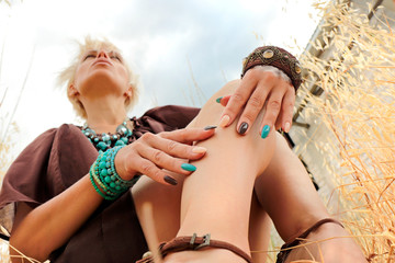 Multi-colored manicure on long oval nails on a woman with brown and blue bracelets on her hands in summer on nature.