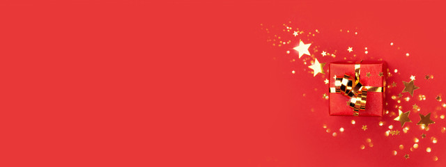 Banner with red gift box with golden bow on red background decorated golden stars confetti. Top view, minimal styled Christmas and holiday concept. Fototapete