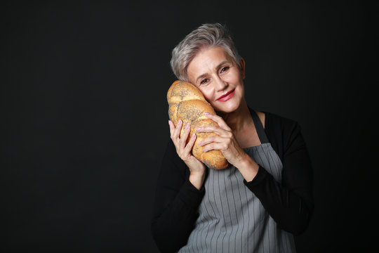beautiful aged woman in apron holding bread in her hands