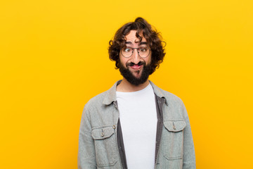 young crazy man looking goofy and funny with a silly cross-eyed expression, joking and fooling around against yellow wall