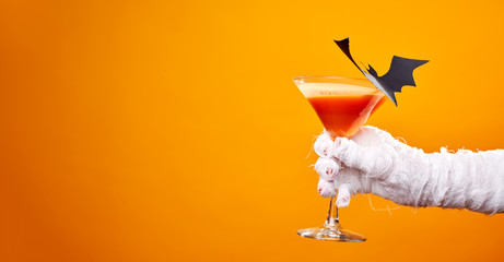 Photo of mummy's hand with wine glass and black bat on empty orange background in studio