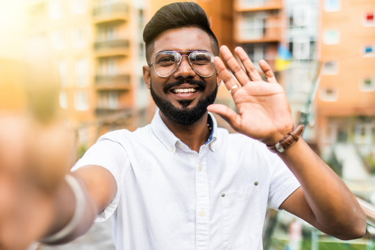Smiling young guy taking selfie photo on smartphone on the street. Indian man using digital device. Selfie photo concept.