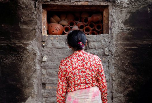 A woman looks towards the earthenwareÕs kept to bake in a traditional oven in Bhaktapur
