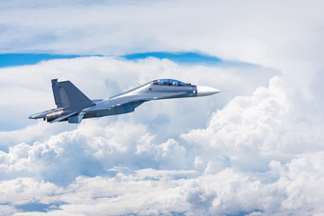 Combat fighter jet flies high in the clouds.