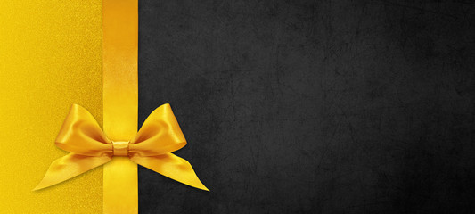 black gift card with golden ribbon bow, black friday concept