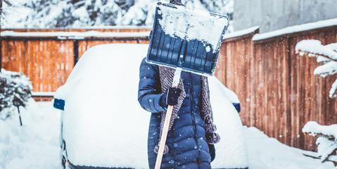 woman with shovel cleaning snow aeound car. Winter shoveling. Removing snow after blizzard
