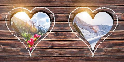 Sommer und Winter Ausblick durch ein Herzfenster  auf einer Alm