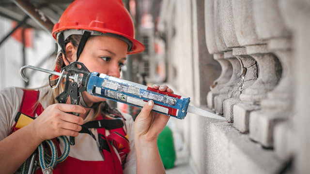 Female construction mason on the scaffolding, working with silicone gun