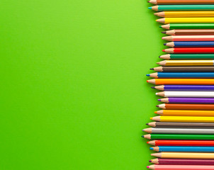 Set of colored pencils next to each other, top view. Green background with crayons and copy space for text. Decorative frame, banner template. Business theme.