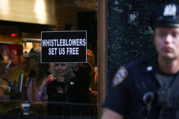A woman holds a sign about whistleblowers in a cafe near U.S. President Trump's motorcade as he attends a campaign fundraiser nearby in New York