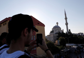 A man takes pictures of a damaged mosque after an earthquake in Istanbul