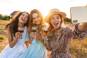 Photo of delighted nice women taking selfie photo on cellphone