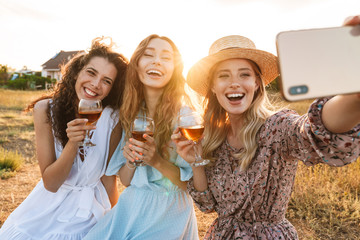 Photo of delighted pretty women taking selfie photo on cellphone