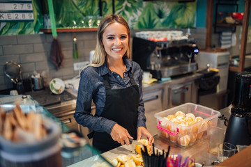 Wall Murals Juice Portrait of a beautiful smiling woman working at juice bar.