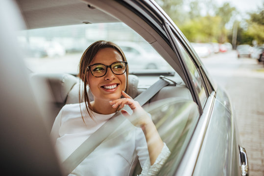 Portrait of a happy young woman in back seat of car looking out of window.