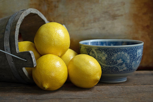 Original textured still life photograph of lemons pouring out of a wooden bucket with a blue china bowl on brown