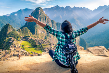 A woman tourist contemplating the amazing landscape of Machu Picchu with arms open. Archaeological site, UNESCO World Heritage