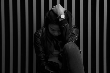 Portrait of asian girl are sitting on the floor beside the wall and looked sad. Black and white images of Thai women are suffering from depression.