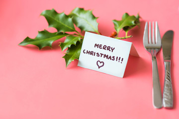 Merry Christmas text on blue card among silverware and christmas decorations on pink background