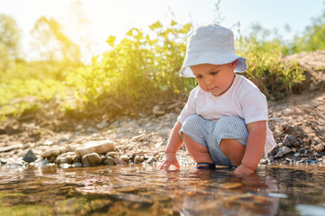 Portrait of playful small little boy child playing with rocks and water by the lake or river in sunny day wearing hat in nature