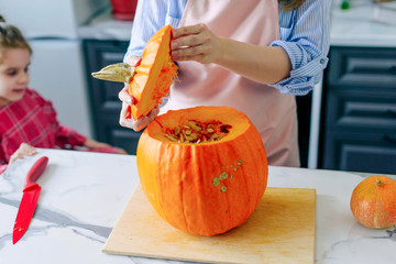 Happy family mother and child happy girl is cutting a pumpkin and is preparing for the holiday Halloween.Happy Halloween. Recipe pumpkin puree. Ingredients for pumpkin pie for Thanksgiving day. Wall mural